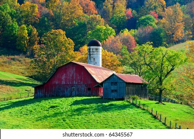 picturesque red barn in front of beautiful autumn fall colorful trees