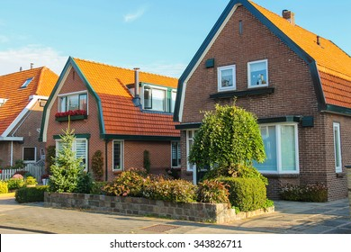Picturesque residential houses with decorative plants before them in small Dutch town Zwanenburg, the Netherlands