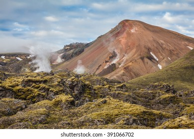 Picturesque rhyolite mountains surround the valley. In the hollows of the mountains from the ground rises steam.  Summer morning in the National Park Landmannalaugar, Iceland