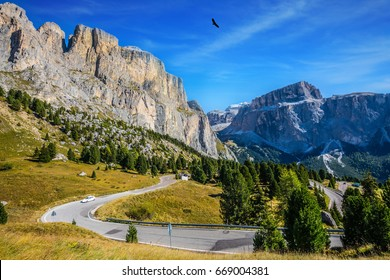 """Picturesque road through the Sella Pass, Dolomites. The concept of extreme and ecological tourism. Impressive ridge of dolomite rocks. """"Indian summer"""" in the Tyrol"""