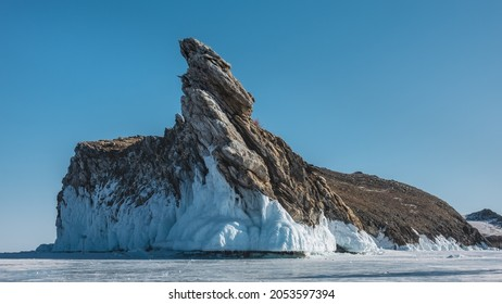 A picturesque rock, devoid of vegetation, rises on a frozen lake against the blue sky. Bizarre shapes, cracks on the stones. The base is covered with a thick layer of icicles. Baikal.