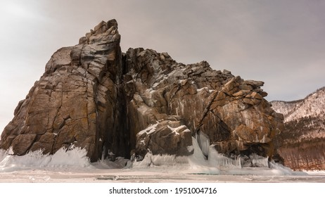 A picturesque rock without vegetation, with steep slopes and many cracks rises on a frozen lake. At the base of the cliff there are ice splashes, icicles. Sepia shades. Baikal