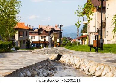 Picturesque scene of Bansko Ski Resort in the Pirin Mountains in Bulgaria with a view along a stone channel of a stream flowing past typical traditional houses on a sunny summer day