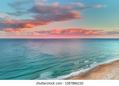 Picturesque scenery aerial drone point view landscape, calm blue Mediterranean Sea colourful fluffy glowing pink clouds at sunset evening sky, sandy coastline. La Mata, Torrevieja, Costa Blanca, Spain