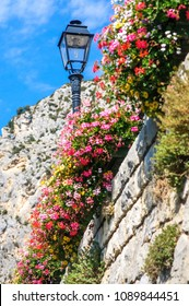 Picturesque scenery on an old wall with colorful flowers in a village of South of France