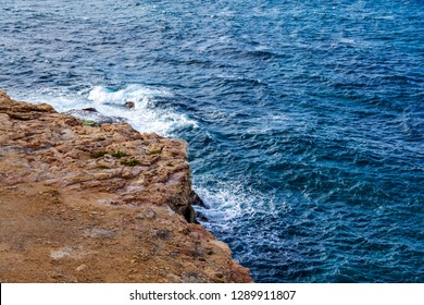 Picturesque sea waves with foam near the rocky coast of the Mediterranean Sea