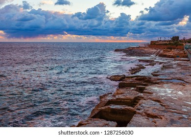 Picturesque sea waves near the rocky coast of the Mediterranean Sea are lit with the dawn sun