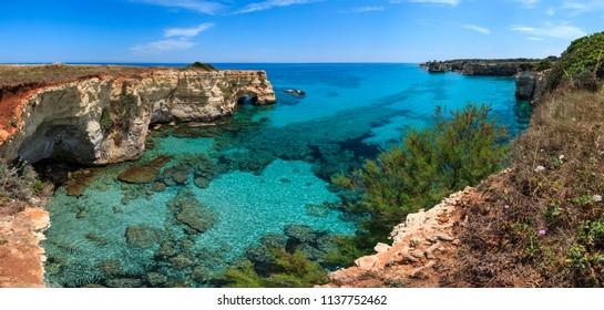 Picturesque seascape with cliffs, rocky arch and stacks (faraglioni), at Torre Sant Andrea, Salento sea coast, Puglia, Italy