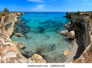 Picturesque seascape with cliffs, rocky arch and stacks (faraglioni), at Torre Sant Andrea, Salento sea coast, Puglia, Italy