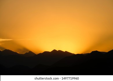 Picturesque silhouettes of high mountains of Tibet at sunrise. Golden morning sun gently illuminates the mountain range in Himalaya. Golden evening sun hides behind a ridge in the Himalayas