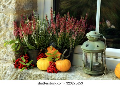 Picturesque small decoration in farm in Poland. Pumpkin, heathers and lantern on window. Autumn crops.
