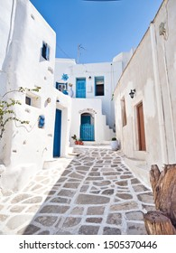 Picturesque southern cobbled street with white houses and bright blue doors in Lefkes Paros Greece on summer sunny day
