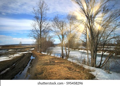 picturesque spring landscape with river ice melted bare trees and beautiful clouds in the blue sky