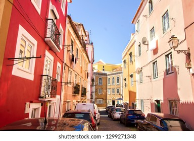 Picturesque street in Alfama, Lisbon, Portugal. Brightly colored buildings lit by the morning sun.