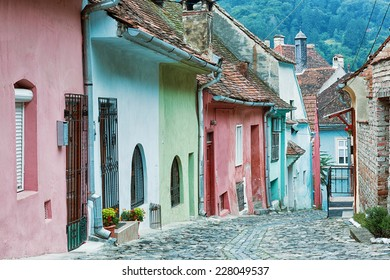 Picturesque street with pastel coloured houses in Sighisoara, Romania.