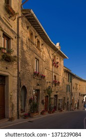 Picturesque street of preserved medieval pilgrimage town Assisi in region Umbria in Italy, birthplace of saint Francis and Clare of Assisi, with old stone houses with flowers in flower pots on walls