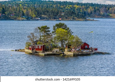 Picturesque summer houses painted in traditional falun red on dwellings island in Stockholms Skärgården (Stockholm Archipelago) in Baltic sea at spring sunny morning.