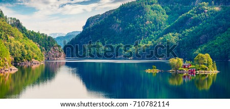 Picturesque summer panorama with small island with typical Norwegian building on Lovrafjorden fjord, North sea. Colorful morning view in Norway. Beauty of nature concept background.