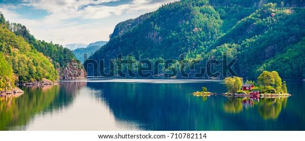 Malerisches Sommerpanorama mit kleiner Insel mit typisch norwegischem Gebäude auf dem Fjord Lovrafjorden, Nordsee. Farbige Aussicht auf den Morgen in Norwegen. Schönheit des Naturkonzepts Hintergrund.