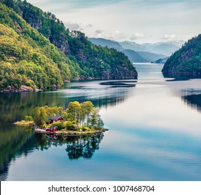 Picturesque summer view of small island with red painted Norwegian building on Lovrafjorden flord, North sea. Colorful morning view in Norway. Beauty of nature concept background.