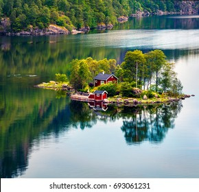 Picturesque summer view with small island with typical Norwegian building on Lovrafjorden fjord, North sea. Colorful morning view in Norway. Beauty of nature concept background.