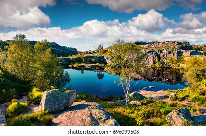 Picturesque summer view of small lake on the mountain plateau. Colorful morning scene on the Norway countryside. Beauty of nature concept background.