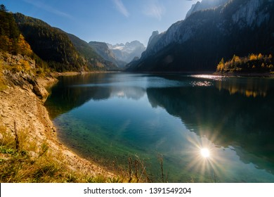 Picturesque sunny view on Gosausee (Vorderer) Lake, Dachstein mountains and sun reflected in the water. UNESCO World Heritage. Location place: Salzkammergut region, Upper Austria.