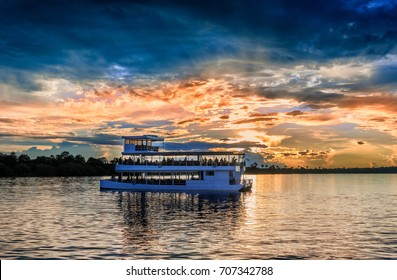 Picturesque sunset  landscape with the riverboat at Zambezi river near Livingstone in Zambia