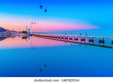 Picturesque sunset over The Park of the Nations in Lisbon, Portugal. Evening cityscape with cable car road and bridge reflected in water