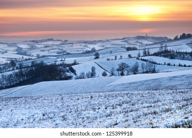 Picturesque sunset in piedmont hillside landscape covered with snow