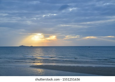 A picturesque tropical gold-coloured crepuscular rays cloudy coastal sunrise seascape in a blue/grey dawn sky over the ocean with seawater reflections. Sunbeams nature background. Huay Yang, Thailand.