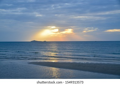 A picturesque tropical white coloured cirrostratus cloudy coastal sunrise seascape in a pale blue sky with yellow crepuscular rays over the ocean with seawater reflections. Huay Yang, Thailand.