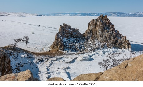 A picturesque two-headed mountain devoid of vegetation rises above the frozen Lake Baikal. Cracks on steep slopes. A motor road on the snowy ice. Clear blue sky. Mount Shamanka.