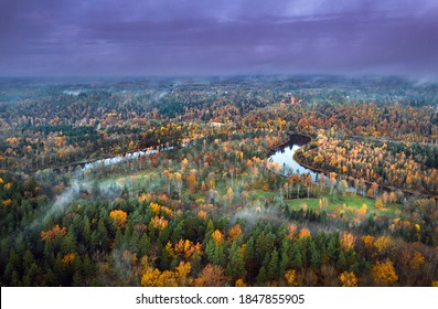 Picturesque valley of colorful trees in Sigulda. Morning mist covering forest and river Gauja.