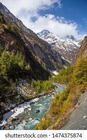 A picturesque valley with mountain river and snow-covered tops of the mountains in the Nepalese Himalayas on the Annapurna Circuit trek.