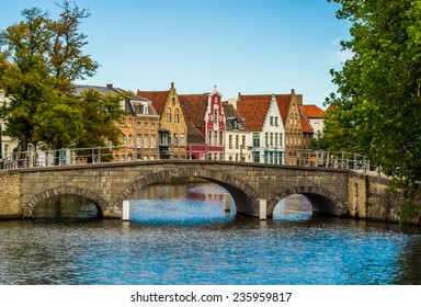 Picturesque view across a bridge to historic brickwall town houses in the famous belgian city of Brugge.