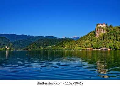 Picturesque view of the Bled Castle and the Bled island surrounded by the Lake Bled. The island has several buildings, one being the pilgrimage church dedicated to the Assumption of Mary.