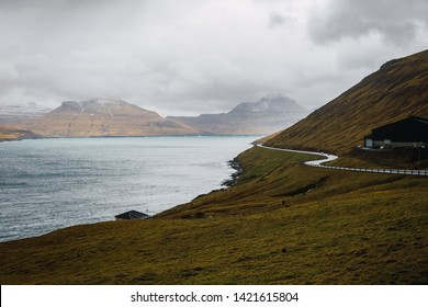 Picturesque view of grassy hill slope with winding asphalt road near calm sea water on cloudy day on Faroe Islands