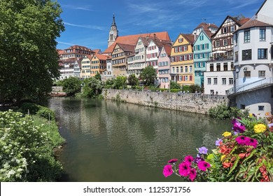 Picturesque view of the historical houses across the riverside of Neckar in the university town of Tubingen, Germany. View from bridge decorated with multicolored natural flowers.