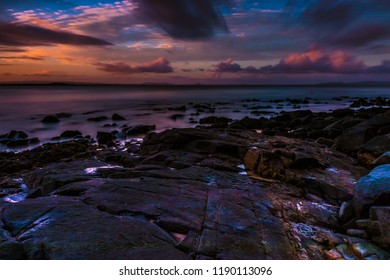 Picturesque view of huge rocks on coast of tranquil ocean in sunset time, Queensland