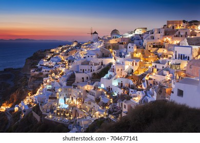 Picturesque view, illuminated Old Town of Oia or Ia on the island Santorini, white houses, windmills and church with blue domes at sunset and twilight. Volcano Santorini, Cyclades islands, Greece, EU