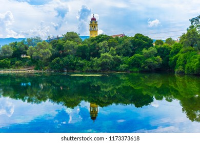 Picturesque view of Karavomilos lake at Sami in Kefalonia ionian island of Greece. Perfect reflection of the cloudscape, the trees and church on the calm waters of the lake