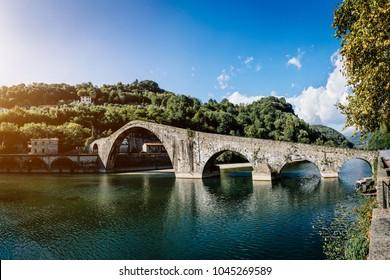 Picturesque view of medieval stone arch bridge Ponte della Maddalena across river Serchio in Borgo a Mozzano, Lucca, Tuscany, Italy. Scenic travel destination postcard.