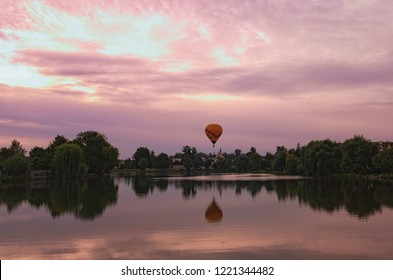 Picturesque view of medieval Telc during magic sunrise. One hot air balloon flies over the houses and reflected on smooth lake water. Summer landscape. Telc, Southern Moravia, Czech Republic.