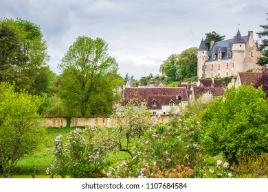 Picturesque view of Montresor village with its castle seen through charming garden with blooming lilac shrubs. Indre-et-Loire, France.