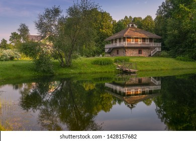 Picturesque view of the old manor reflected in a beautiful pond. Wooden ancient Russian house. Pushkin's family nest. Summer sunny day. Blue calm sky. Pskov. Pushkin mountains. Petrovskoe.