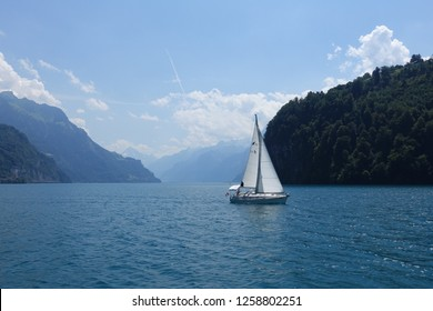 A picturesque view on Swiss Alps from lake Vierwaldstattersee with a sailing boat appearing at the horizon, Lucerne (Luzern), Switzerland