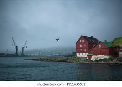 Picturesque view to the Skansapakkhusið the seat of the Faroese government at the tip of Tinganes peninsula on Island Streymoy of the Faroe Islands and Torshavn Port cranes over the Eystara Vág.