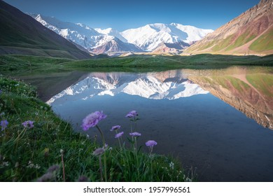 Picturesque view of snowcapped Lenin Peak mountain massif seen from the Achik-Tash base camp with reflection in the glacier lagoon, on the border of Kyrgyzstan and Tajikistan, Central Asia.