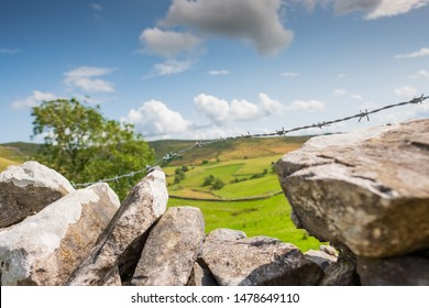 Picturesque view of the stunning Yorkshire Dales as seen from a stone wall. In focus barbed wire is seen in the foreground to prevent trespassers.
